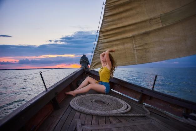 Porträt des jungen schlanken mädchens auf sonnenuntergang im meer. junge frau trifft sonnenaufgang auf boot