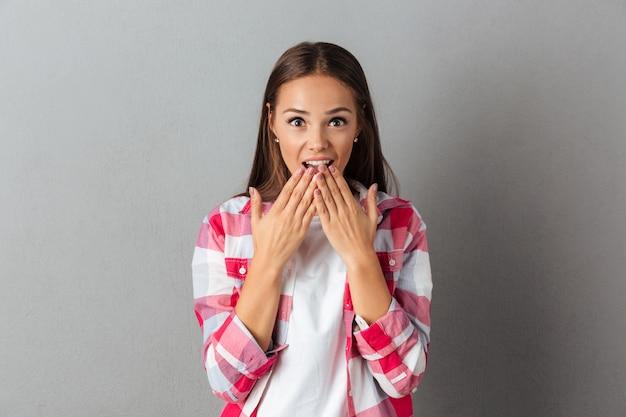 Porträt des jungen schockierten brünetten mädchens, das überrascht ihren mund bedeckt
