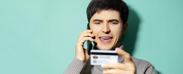 Porträt des jungen schockierten kerls, der auf smartphone mit kreditkarte in der hand auf hintergrund der farbe aqua menthe spricht.