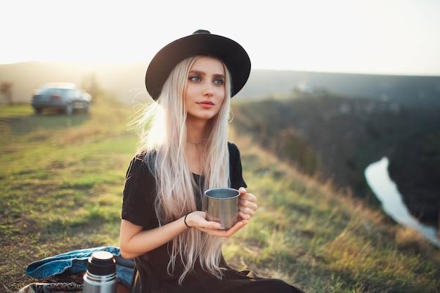 Porträt des jungen schönen blonden mädchens, das eine warme stahlschale mit tee auf dem sonnenuntergang in den bergen nahe fluss hält. trage schwarzen hut und kleid.
