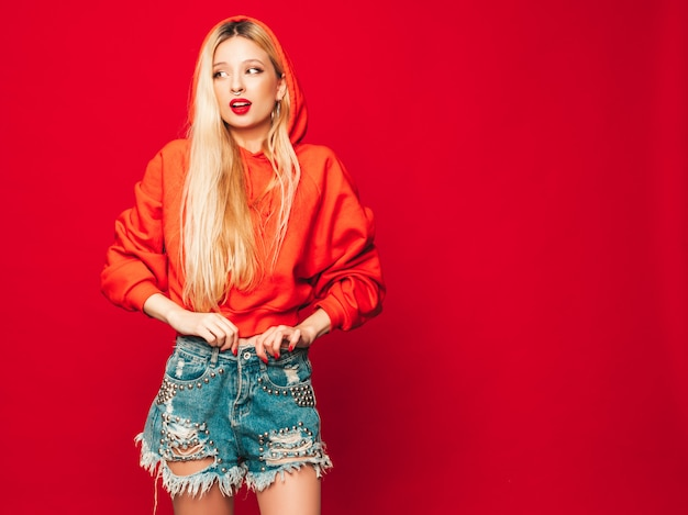 Porträt des jungen schönen bösen hipster-mädchens im trendigen roten kapuzenpulli und im ohrring in der nase. positives model, das spaß hat