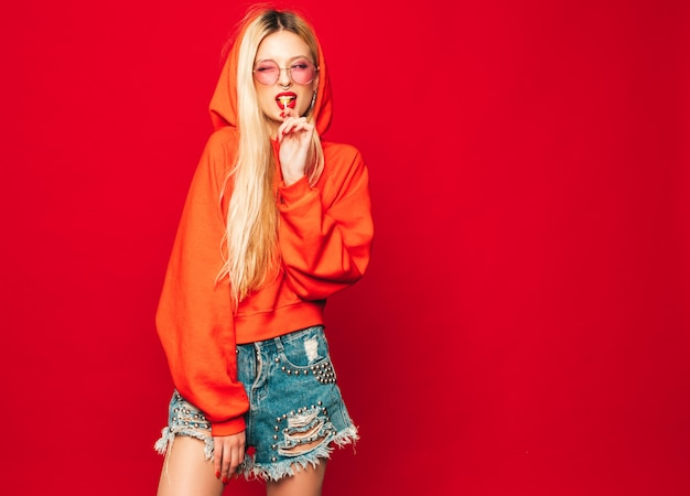 Porträt des jungen schönen bösen hipster-mädchens im trendigen roten kapuzenpulli und im ohrring in der nase. positives modell leckt runde kandiszucker