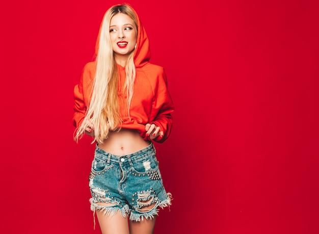 Porträt des jungen schönen bösen hipster-mädchens im trendigen roten kapuzenpulli und im ohrring in der nase. positives modell