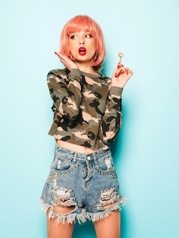 Porträt des jungen schönen bösen hipster-mädchens in den trendigen jeansshorts und im ohrring in der nase. positives modell, das runde kandiszucker leckt