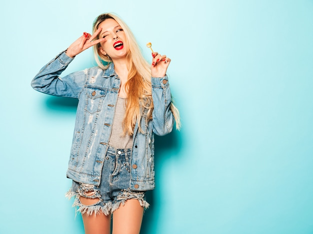 Porträt des jungen schönen bösen hipster-mädchens in der sommerkleidung der trendigen jeans und im ohrring in ihrer nase. positives modell leckt runde kandiszucker