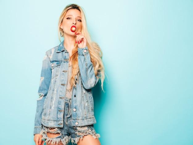 Porträt des jungen schönen bösen hipster-mädchens in der trendigen jeanskleidung und im ohrring in der nase. positives modell leckt runde kandiszucker