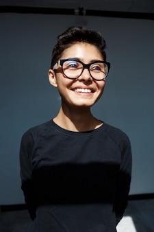 Porträt des jungen schönen brünetten mädchens in den lächelnden gläsern.