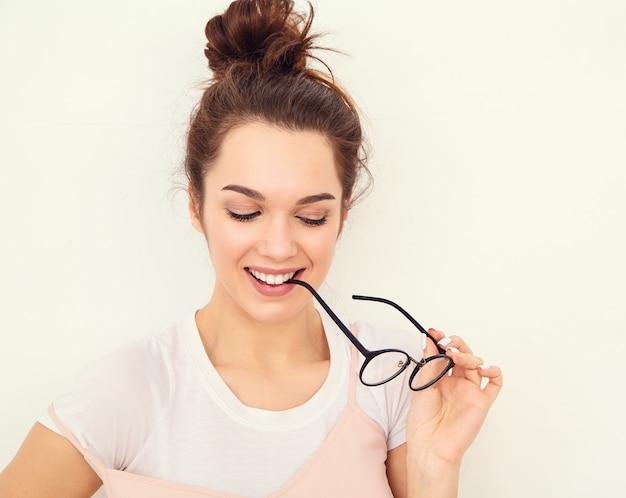 Porträt des jungen schönen brunettefrauen-mädchenmodells mit nacktem make-up im bunten sommerrosahippie kleidet die aufstellung nahe wand. brille beißen