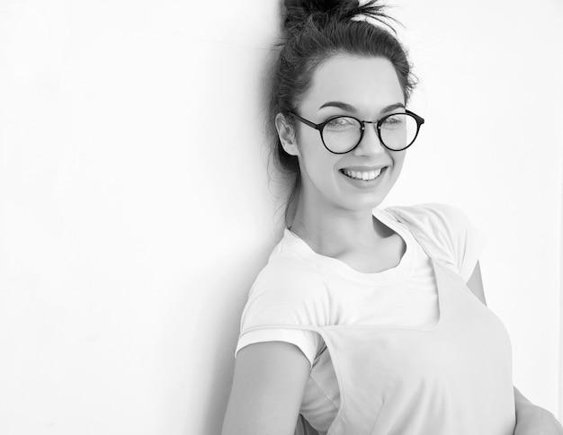 Porträt des jungen schönen brunettefrauen-mädchenmodells mit nacktem make-up im bunten sommerrosahippie kleidet die aufstellung nahe wand. glücklich aussehend