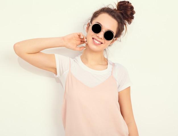 Porträt des jungen schönen brunettefrauen-mädchenmodells mit nacktem make-up im bunten sommerrosahippie kleidet in der sonnenbrille, die nahe wand aufwirft. glücklich aussehend