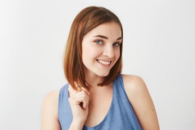 Porträt des jungen schönen glücklichen mädchens mit natürlichem make-up lächelndem berührendem haar.