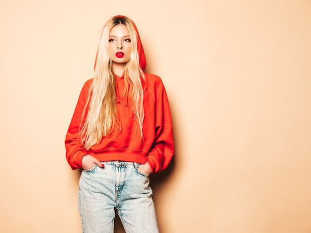 Porträt des jungen schönen hipster bösen mädchens im trendigen roten kapuzenpulli und im ohrring in der nase. sexy sorglose blonde frau, die im studio aufwirft. positives modell, das spaß hat
