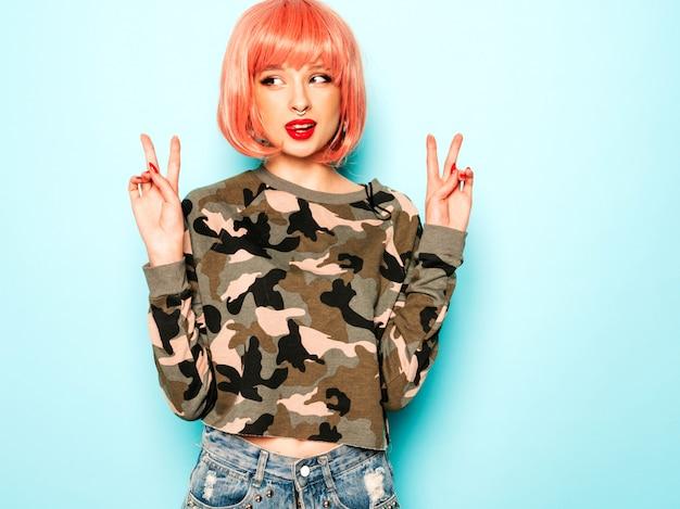Porträt des jungen schönen hipster bösen mädchens in den trendigen jeansshorts und im ohrring in ihrer nase. sexy sorglose lächelnde frau, die im studio in der rosa perücke aufwirft. positives modell, das spaß hat. zeigt friedenszeichen
