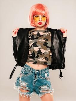 Porträt des jungen schönen hipster bösen mädchens in der schwarzen lederjacke und im ohrring in ihrer nase. sexy sorglose lächelnde frau, die im studio in der rosa perücke nahe blauer wand sitzt. selbstbewusstes modell in der sonnenbrille