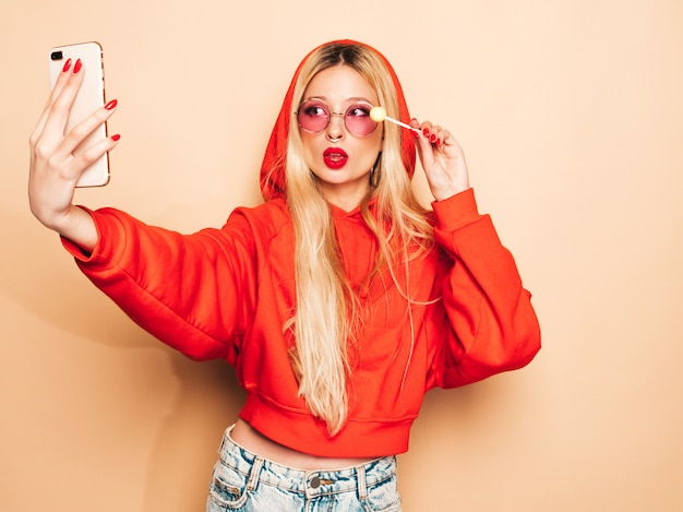 Porträt des jungen schönen hipster bösen mädchens in der trendigen jeans kleidung und ohrring in der nase. sexy sorglos lächelnde blonde frau nimmt selfie. positives modell lecken runde kandiszucker