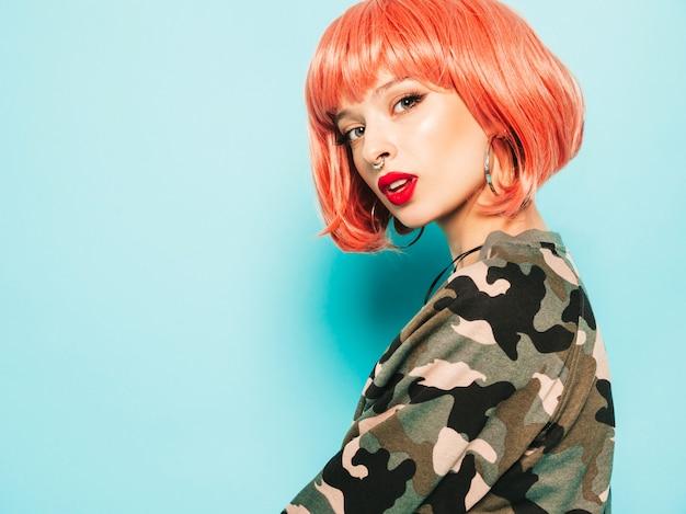 Porträt des jungen schönen hipster bösen mädchens in der trendigen roten sommerkleidung und im ohrring in der nase. sexy sorglose lächelnde frau, die im studio in der rosa perücke nahe blauer wand aufwirft. positives modell, das spaß hat