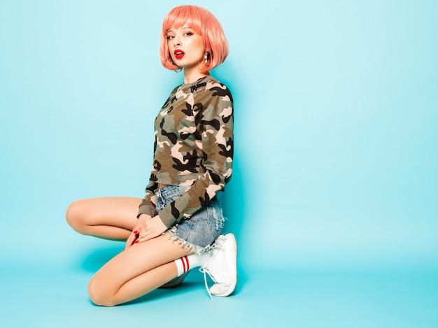 Porträt des jungen schönen hipster bösen mädchens in der trendigen roten sommerkleidung und im ohrring in der nase. sexy sorglose lächelnde frau, die im studio in der rosa perücke nahe der blauen wand sitzt. positives modell, das spaß hat