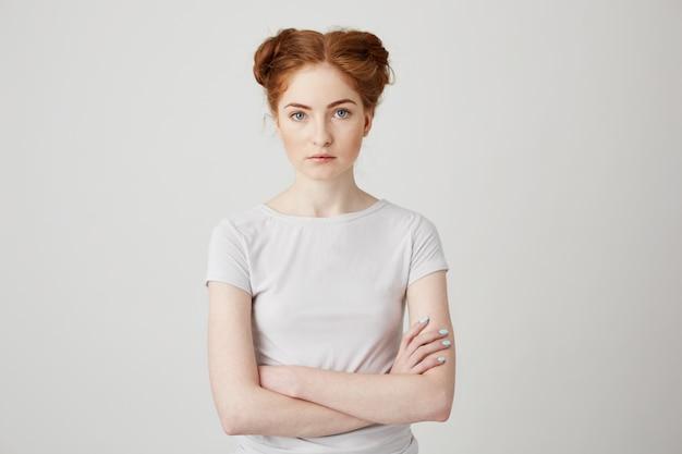 Porträt des jungen schönen ingwermädchens mit brötchen mit verschränkten armen.