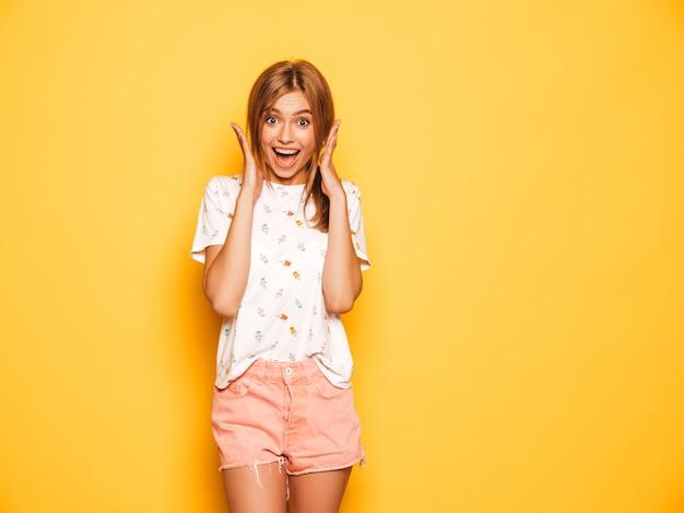 Porträt des jungen schönen lächelnden hippie-mädchens in der modischen sommerjeans-kurzen hosen kleidet. sexy sorglose frau, die nahe gelber wand aufwirft. positives modell, das spaß hat. entsetzt und überrascht