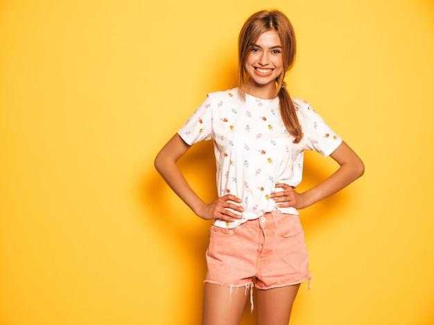 Porträt des jungen schönen lächelnden hippie-mädchens in der modischen sommerjeans-kurzen hosen kleidet. sexy sorglose frau, die nahe gelber wand aufwirft. positives modell, das spaß hat