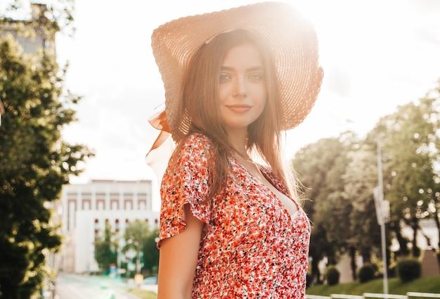 Porträt des jungen schönen lächelnden hipster-mädchens im trendigen sommer-sommerkleid. sexy sorglose frau, die auf dem straßenhintergrund im hut bei sonnenuntergang aufwirft. positives modell im freien