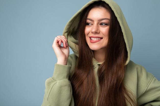 Porträt des jungen schönen lächelnden mädchens im grünen hoodie des stilvollen hippies. sexy sorglose frau, die nahe blauer wand aufwirft. positives model hat spaß