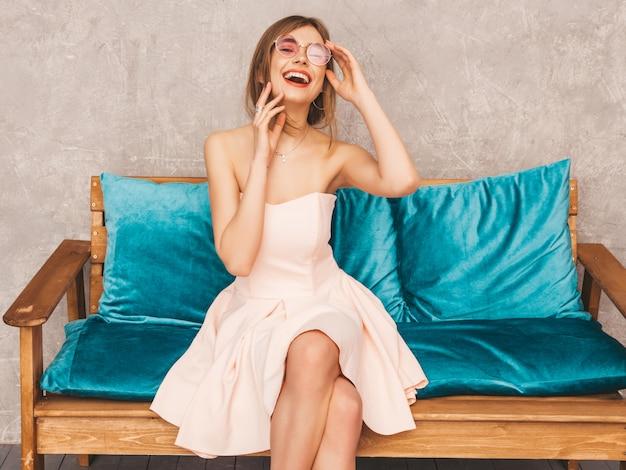 Porträt des jungen schönen lächelnden mädchens im hellrosa kleid des modischen sommers. sexy sorglose frau, die auf hellem blauem sofa sitzt. posing in luxusausstattung