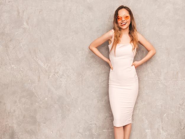 Porträt des jungen schönen lächelnden mädchens im hellrosa kleid des modischen sommers. sexy sorglose frauenaufstellung. positives modell, das spaß hat und ihre zunge zeigt
