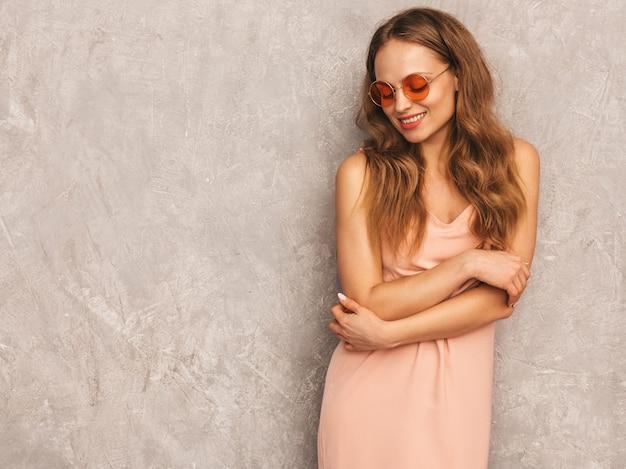 Porträt des jungen schönen lächelnden mädchens im hellrosa kleid des modischen sommers. sexy sorglose frauenaufstellung. positives modell, das spaß hat
