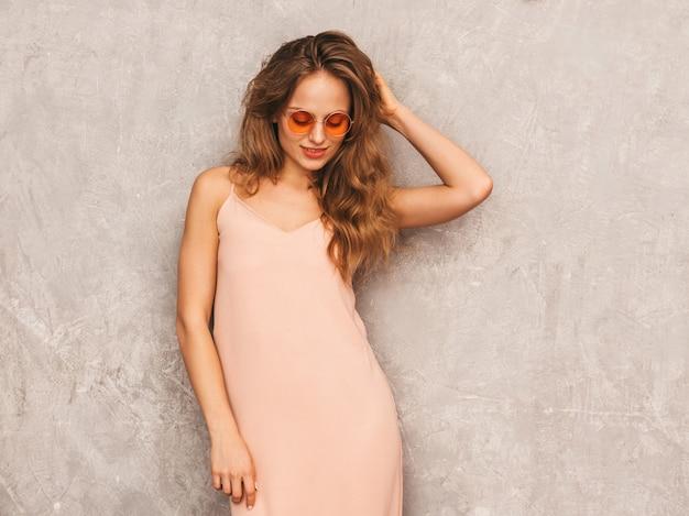 Porträt des jungen schönen lächelnden mädchens im hellrosa kleid des modischen sommers. sexy sorglose frauenaufstellung. positives modell, das spaß in der runden sonnenbrille hat