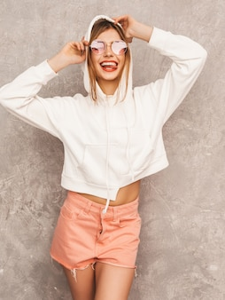 Porträt des jungen schönen lächelnden mädchens im modischen sommersport kleidet. sexy sorglose frauenaufstellung. positives modell, das spaß in der sonnenbrille hat