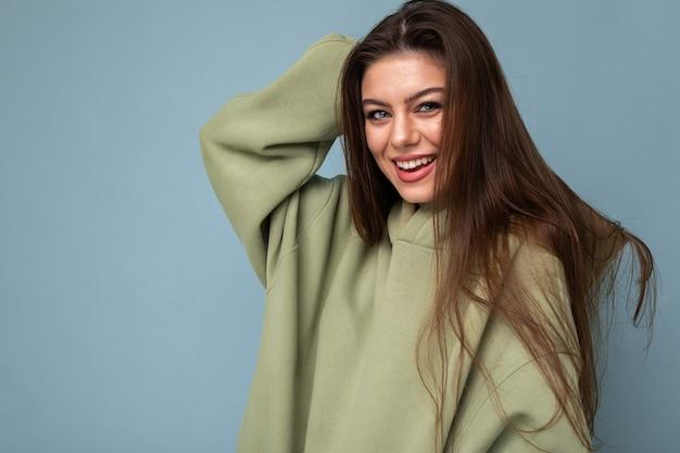 Porträt des jungen schönen lächelnden mädchens im stilvollen grünen kapuzenpulli des hipsters. sexy sorglose frau, die nahe blaue wand aufwirft