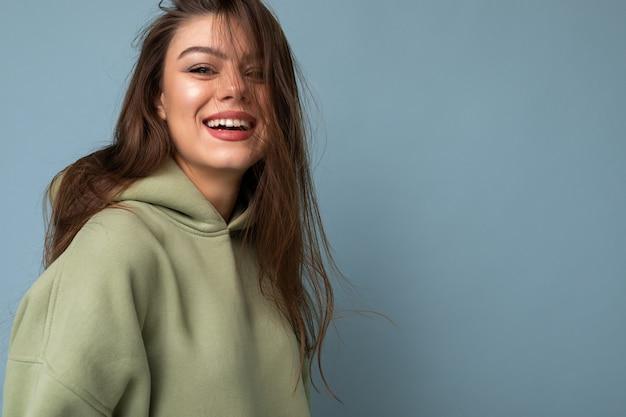 Porträt des jungen schönen lächelnden mädchens im stylischen hippie-grün hoodie hood