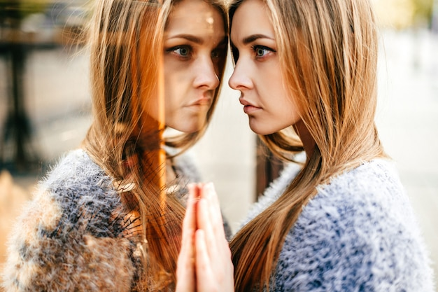 Porträt des jungen schönen langhaarigen mädchens mit dem emotionalen gesicht, das ihre reflexion in widergespiegeltem schaukasten betrachtet.