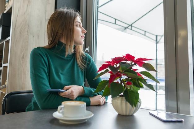 Porträt des jungen schönen mädchens, das am café sitzt