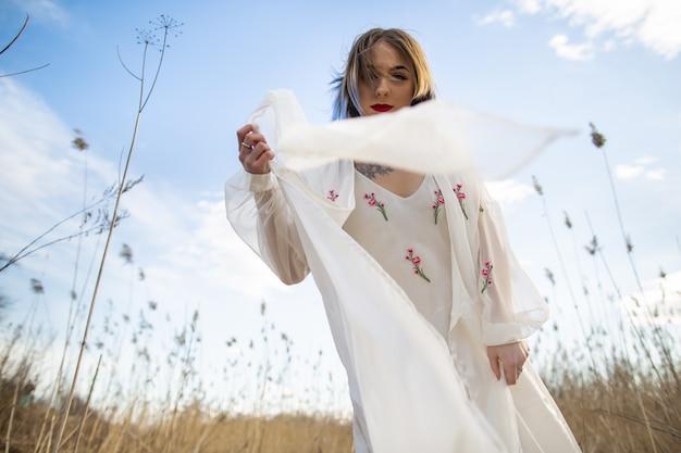 Porträt des jungen schönen mädchens im weißen kleid auf dem weizengebiet, gehend, sorglos.
