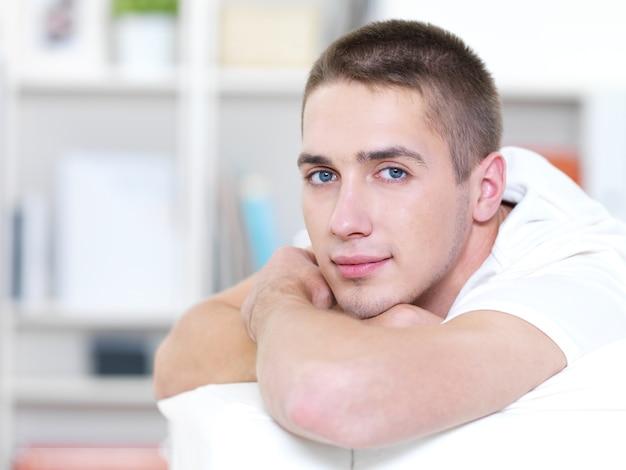 Porträt des jungen schönen mannes, der auf dem sofa liegt
