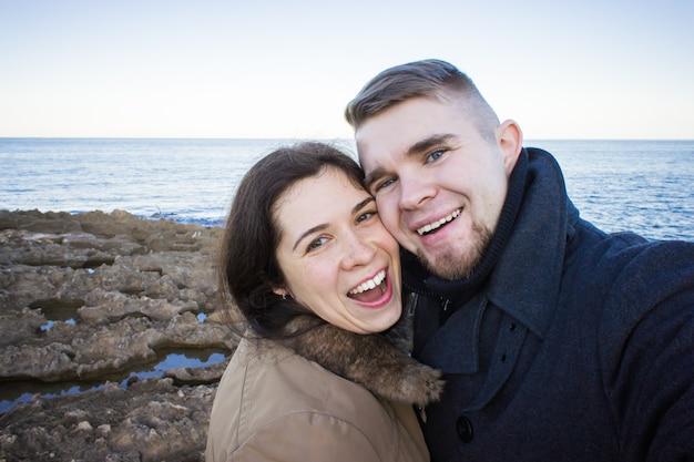 Porträt des jungen schönen paares, das selfie-foto in einem smartphone mit meer und dunklem bewölktem himmel auf dem hintergrund nimmt. kalte jahreszeit und reisekonzept.