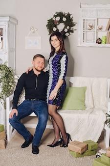 Porträt des jungen schönen paares verliebt in schöne outfits, die für ein neujahrsfoto-shooting zu hause posieren
