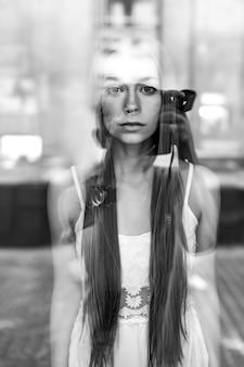 Porträt des jungen schönen romantischen brünetten mädchens mit dem langen haar, das hinter glas aufwirft