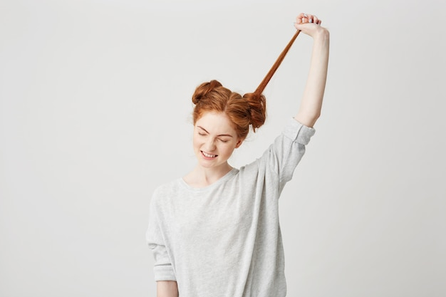 Porträt des jungen schönen rothaarigen mädchens lösen brötchen, das haare berührt.