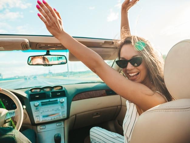 Porträt des jungen schönen und lächelnden hippie-mädchens im umwandelbaren auto