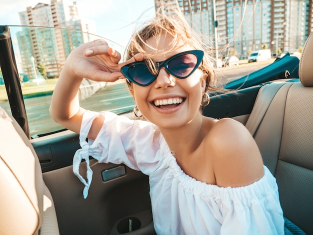 Porträt des jungen schönen und lächelnden hippie-mädchens im umwandelbaren auto Kostenlose Fotos