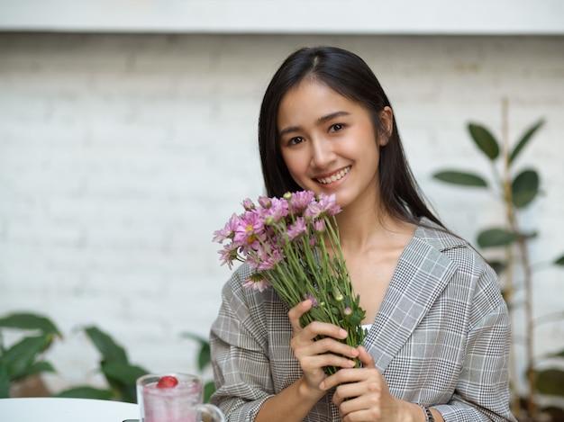 Porträt des jungen schönen weiblichen handrosa-blumenbrunchs und des lächelns zur kamera