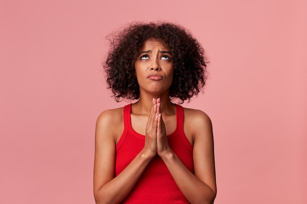 Porträt des jungen schönheits-afroamerikanermädchens mit dem gelockten dunklen haar, das in einem roten t-shirt trägt. lool up, hält die handflächen zusammen, freut sich über die gnade. isoliert.