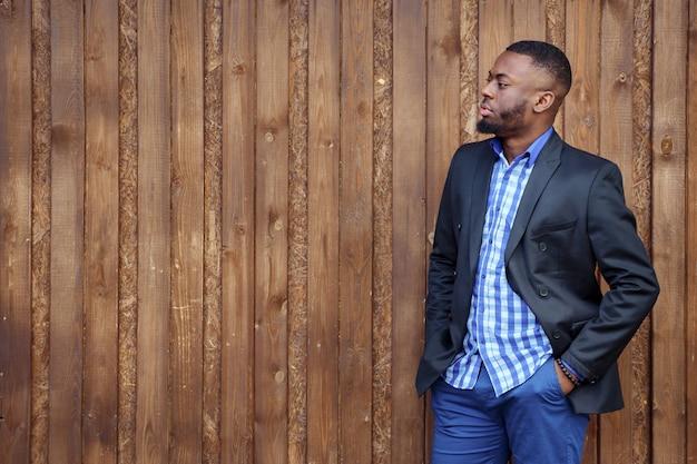 Porträt des jungen schwarzen bärtigen kerls, der und hand in der tasche steht. afroamerikanischer mann im anzug ist selbstbewusst und schaut auf dunklem holzhintergrund weg, kopierraum