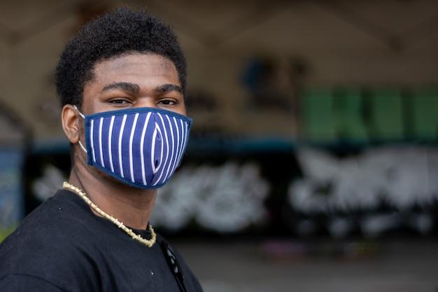 Porträt des jungen schwarzen jungen mit gesichtsmaske. graffiti-wandhintergrund.