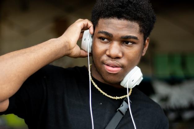 Porträt des jungen schwarzen jungen mit weißen kopfhörern. musik hören. graffiti-wandhintergrund.