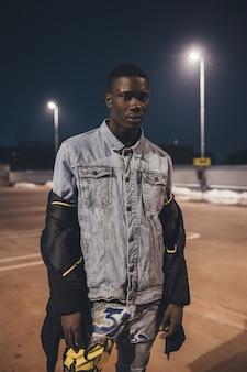 Porträt des jungen schwarzen mannes, der im parkplatz im freien steht