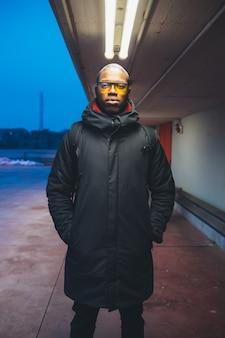 Porträt des jungen schwarzen mannes, der kamera schaut und im freien aufwirft